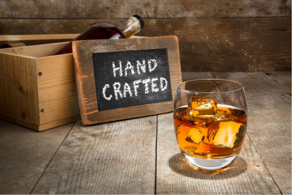 A sign that reads hand crafted with a glass of cocktail in front of it.
